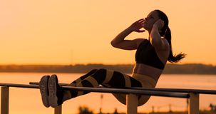 Candid shot of real healthy and fit woman performing hanging leg raises on outdoor fitness station in sunset at beach. Promenade. Showing strong abdominal six stock video