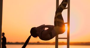 Candid shot of real healthy and fit woman performing hanging leg raises on outdoor fitness station in sunset at beach. Promenade. Showing strong abdominal six stock footage