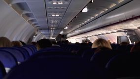 Candid shot between seats of passengers sitting inside airplane while traveling.  stock footage