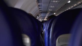 Candid shot between seats of passengers sitting inside airplane while traveling.  stock video footage