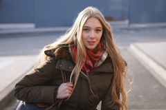 Candid street style portrait of teenage girl waiting at bus stop. On a sunny day in winter stock image