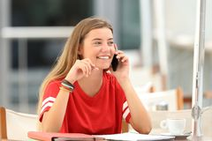 Candid student girl talking on phone in a bar royalty free stock photo