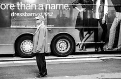 Senior male seen in front of a passing bus with advertising on its side. royalty free stock images