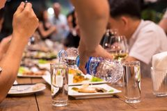 Candid waiter pouring water from bottle while people having dinne. Candin Wwaiter pouring water from bottle while people having dinne at restaurant shot in high royalty free stock images