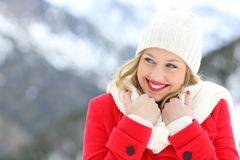 Candid woman keeping warm in winter holiday. Candid woman in red keeping warm and looking at side in winter holiday royalty free stock photos