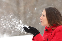 Candid woman in red blowing snow in winter. Side view of a candid woman in red blowing snow in winter during a snowfall Royalty Free Stock Image
