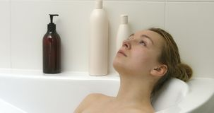 Candid woman relaxing at bath. Candid adult woman relaxing at bath in her bathroom stock video