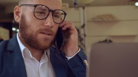 Candid worker call by cellular at work. Handsome redheaded businesman has phone negotiations in office, successful worker in startup company talking by stock video
