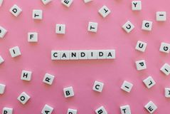 Candida word made of square letter word on pink background. Candida word made of square letter word on pink background stock photos