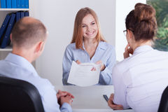 Candidate presenting application. Young female candidate presenting her application on job interview royalty free stock images