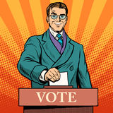 Candidate votes at the elections. Pop art retro style. Male politician at a polling station. The voice of men. The voter at the ballot box stock illustration