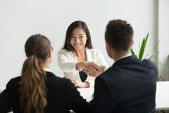 Candidato asiático milenar feliz que obtém contratado agitando a mão de h imagem de stock
