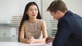 Candidato de trabajo asiático de la empresaria que habla con el encargado de la hora en la entrevista almacen de video