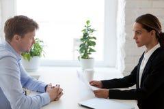 Candidato de trabajo y encargado de la hora que se sienta en el escritorio en la entrevista fotografía de archivo