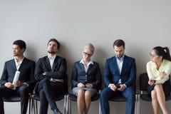 Candidatos de trabalho diversos que sentam a espera na fila pela entrevista imagem de stock