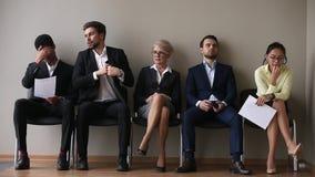 Candidatos diversos a la vacante que se sienta en las sillas que esperan su vuelta almacen de metraje de vídeo