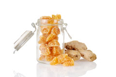 Candied ginger in a jar with root. And reflection Royalty Free Stock Photography