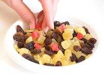 Candied peel, raisins, and women's hand. stock image