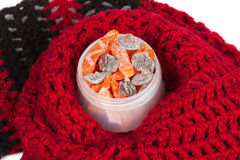 Candied pumpkin in a small pot on a background of red wool scarf. Homemade sweetness of dried fruit. Royalty Free Stock Images