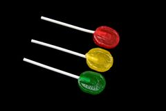 Candies. Three colorful lollipops. Isolated on black background royalty free stock photography