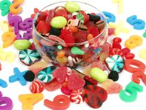 Candies. Colorful pastel candy and play numbers on glass bowl stock image