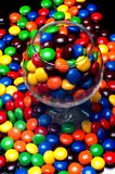Candies. Multicolor candies in a glass and spilling out over the table Stock Photography