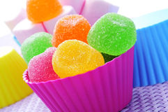 Candies. Some colorful bowls with candies of different colors on a purple woven surface Royalty Free Stock Images