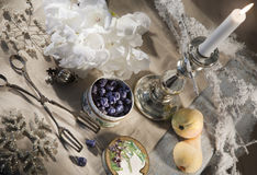 Candies and candleholder. Violet blossom leaves candied in sugar and silver candleholder on a traditionally decorated table during christmastime Stock Photos