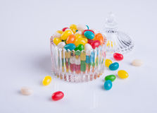 Candies or colorful candies in glass jar on background. Stock Photos