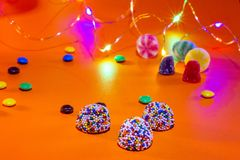 Candies and colorful chocolates on an orange background. Small led lights of colors. Horizontal view Birthday celebration concept stock image