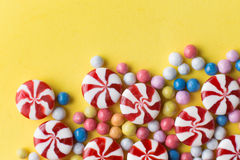 Candies colorful mix on yellow bright background with copy space Stock Photos