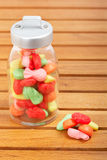 Candies in the glass jar. Colorful candies in the glass jar on wooden background Stock Photography
