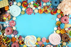 Candies with jelly and sugar. colorful array of different childs sweets and treats on blue. Background royalty free stock photos