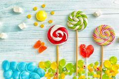 Candies and lollipops. On wooden background royalty free stock photo