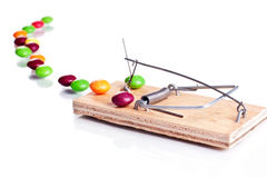 Candies on mousetrap Stock Photos