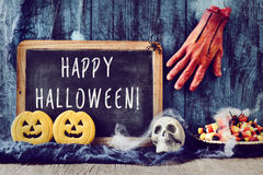 Candies, ornaments and text happy halloween in a chalkboard royalty free stock photography