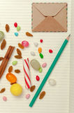 Candies, raisins, cinnamon, pencil and envelope at pages of note Stock Photos
