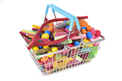 Candies in a shopping basket. A metal shopping basket full of candies with different shapes and flavors on a white background Stock Photos