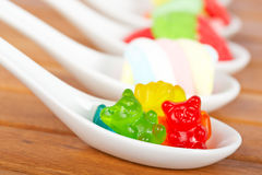 Candies in the spoons Stock Photos