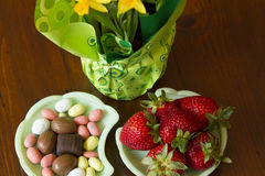 Candies, Strawberries and Daffodils. Daffodils in a green wrapping, with chocolates, candies and strawberries in a kitchen setting Royalty Free Stock Photos