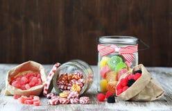 Candies. Sweet sugar candies in glass jars on brown vintage wooden background Stock Photos