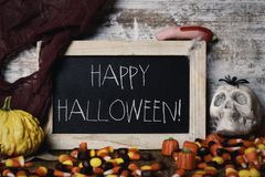 Candies and text happy halloween in a chalkboard Stock Images