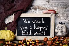 Candies and text We witch you a happy Halloween. A chalkboard with the text We witch you a happy Halloween, placed on a rustic wooden surface next to a skull, a Royalty Free Stock Photos