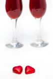 Candies and two glasses of wine. Heart shaped candies and two glasses of red wine on a white background Stock Photos