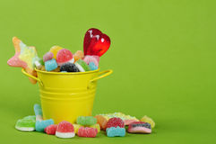 Candies in yellow bucket. Colorful candies in yellow bucket on green background Stock Image
