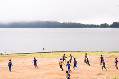 Candikuning: Boys playing football on the lakeside Royalty Free Stock Images