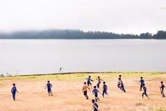 Candikuning: Jongens die voetbal op de oever van het meer spelen Royalty-vrije Stock Afbeeldingen
