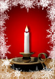 Candle. Isolated burning candle in a brown candle holder encircled by snowflakes Stock Image