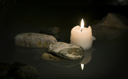Candle. Burning candle in water among stones stock photos