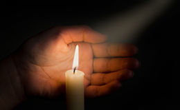 Candle. And hand  on a black background Royalty Free Stock Images